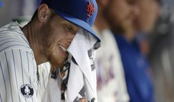 New York Mets starting pitcher Zack Wheeler wipes his face with a towel while sitting in the dugout after allowing six runs on six hits in two innings of an interleague baseball game against the Oakland Athletics in New York, Wednesday, June 25, 2014. The Athletics defeated the Mets 8-5. (AP Photo/Kathy Willens)