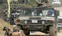 """FILE - In this Saturday, March 3, 2007 file photo, a convoy of armed U.S. humvees stop as goats pass by  during the closing ceremonies of the annual military exercises called """"Balikatan,"""" or """"shouldering the load together,""""  at the coastal village of Bato-Bato in Indanan town, Jolo province, southern Philippines. After more than a decade of helping fight al-Qaida-linked militants, the United States is disbanding an anti-terror contingent of hundreds of elite American troops in the southern Philippines where armed groups such as Abu Sayyaf have largely been crippled, officials said Thursday. (AP Photo/Aaron Favila, File)"""