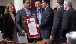 Boxer Oscar De La Hoya, center, poses for pictures with lawmakers left to right, Sen. Ellen Corbett, D-Hayward, Sen. Ben Hueso, D-San Diego, Sen. Kevin de Leon, D-Los Angeles, Sen. Joel Anderson, R-Alpine, and Sen. Jim Nielen, R-Fresno, on the floor of the California State Senate after being honored for his recent induction into the International Boxing Hall of Fame, accomplishments in business and his community service during a ceremony  at the Capitol in Sacramento, Calif., on Thursday, June 26, 2014.(AP Photo/Steve Yeater)