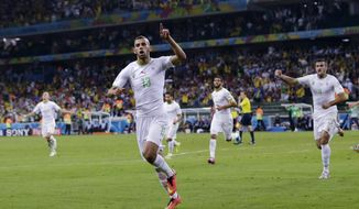 Algeria's Islam Slimani (13) celebrates after scoring during the group H World Cup soccer match between Algeria and Russia at the Arena da Baixada in Curitiba, Brazil, Thursday, June 26, 2014. (AP Photo/Fernando Vergara)