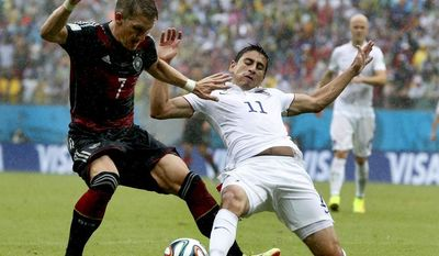 Germany's Bastian Schweinsteiger, left, is challenged by United States' Alejandro Bedoya, right, during the group G World Cup soccer match between the USA and Germany at the Arena Pernambuco in Recife, Brazil, Thursday, June 26, 2014. (AP Photo/Matthias Schrader)