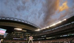 The twilight sky is seen through the retracted roof of Safeco Field as relief pitcher Tom Wilhelmsen pitches to Boston Red Sox's Dustin Pedroia in the seventh inning of a baseball game, Wednesday, June 25, 2014, in Seattle. (AP Photo/Ted S. Warren)