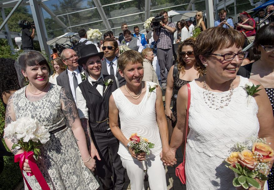 Newlyweds celebrate after over 100 gay couples participated in a mass wedding during World Pride 2014 at Casa Loma in Toronto, Thursday, June 26, 2014.  (AP Photo/The  Canadian Press, Darren Calabrese)