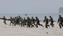 ** FILE ** In this Friday, May 9, 2014, photo, U.S. and Philippine marines storm the beach to simulate a raid during the joint U.S.-Philippines military exercise dubbed Balikatan 2014 at the Naval Training Exercise Command, a former U.S. naval base, and facing the South China Sea at San Antonio township, Zambales province northwest of Manila, Philippines. (AP Photo/Bullit Marquez)