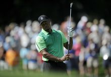 Tiger Woods reacts on the 17th fairway during the first round of the Quicken Loans National golf tournament, Thursday, June 26, 2014, in Bethesda, Md. (AP Photo/Nick Wass)