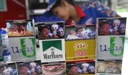 FILE - In this June 24, 2014 file photo, new packs of cigarettes displaying pictorial health warnings are arranged on the counter by a shop attendant for photographers at a convenience store in Jakarta, Indonesia. Tobacco companies on Tuesday largely snubbed an Indonesian law requiring them to put graphic photo warnings on all cigarette packs being sold, marking another setback in a country that's home to the world's highest rate of men smokers and a wild, wild west of advertising. (AP Photo/Tatan Syuflana, File)