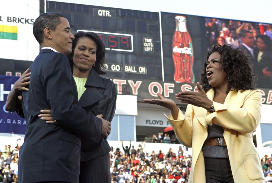 Democratic presidential hopeful, Sen. Barack Obama, D-Ill., hugs his wife Michelle as they are joined by Oprah Winfrey during a rally in Columbia, S.C., Sunday, Dec. 9, 2007. (AP Photo/Gerry Broome)