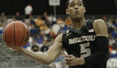 Missouri guard Jordan Clarkson (5) passes the ball against Florida center Patric Young (4) during the first half of an NCAA college basketball game in the quarterfinal round of the Southeastern Conference men's tournament, Friday, March 14, 2014, in Atlanta. (AP Photo/Steve Helber)