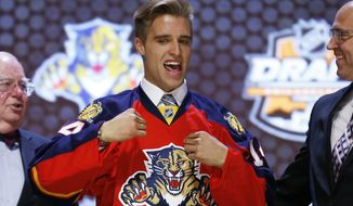 Aaron Ekblad pulls on a Florida Panthers sweater after being chosen first overall in the NHL hockey draft, Friday, June 27, 2014, in Philadelphia. (AP Photo/Matt Slocum)
