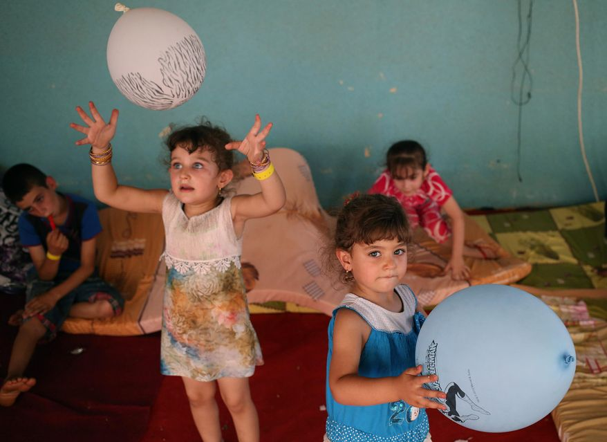 Displaced Iraqi Christian girls who fled with their parents from the Christian village near Mosul province in Iraq, play by their balloons at a temporary shelter for the displaced Christian families in Ankawa, a suburb of Irbil, with a majority Christian population, Iraq. (AP Photo/Hussein Malla)