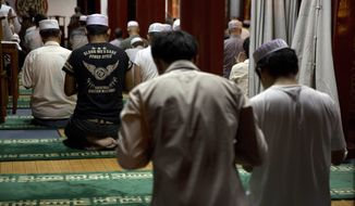 Chinese Muslims attend a prayer session to mark the start of Ramadan at the Niujie mosque, the oldest and largest mosque in Beijing, China, Saturday, June 28, 2014. Muslims throughout the world start observing the holy month of Ramadan, when the observant refrain from eating, drinking, smoking and sex from dawn to dusk. (AP Photo/Ng Han Guan)