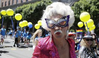 A man dressed in drag marches with a group of employees and family members with Kaiser Permanente during the 44th annual San Francisco Gay Pride parade Sunday, June 29, 2014, in San Francisco. The lesbian, gay, bisexual, and transgender celebration and parade is one of the largest LGBT gatherings in the nation. (AP Photo/Eric Risberg)