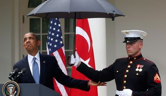 Pay no attention to the umbrella: President Obama says sunny days are here again. (Associated Press)