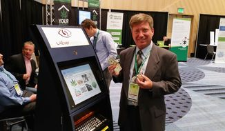 Mark Goldfogel, CEO of C4EverSystems, demonstrates a banking kiosk designed for marijuana retailers who have difficulty gaining access to banking. His invention allows customers to deposit funds directly into a cash box. (Valerie Richardson/The Washington Times)
