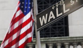 The American flag and Wall St. street sign outside the New York Stock Exchange, in New York.  (AP Photo/Mark Lennihan, File)