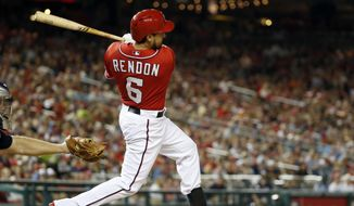 Washington Nationals' Anthony Rendon follows through on his RBI double during the seventh inning of a baseball game against the Atlanta Braves at Nationals Park on Saturday, June 21, 2014, in Washington. The Nationals won 3-0. (AP Photo/Alex Brandon)