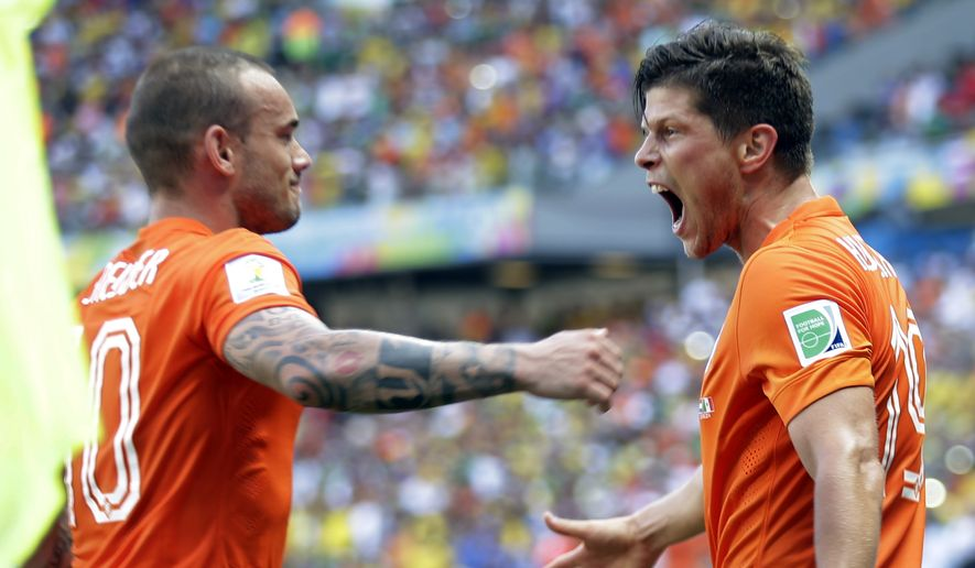 Netherlands' Klaas-Jan Huntelaar, right, celebrates with Wesley Sneijder after scoring his side's second goal during the World Cup round of 16 soccer match between the Netherlands and Mexico at the Arena Castelao in Fortaleza, Brazil, Sunday, June 29, 2014. The Netherlands won the match 2-1. (AP Photo/Natacha Pisarenko)