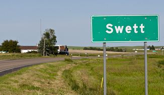 In this June 26, 2014, photo, a road marker highlights Swett, S.D.'s small borders. A businessman is selling the small, southwestern South Dakota town for $400,000. (AP Photo/Rapid City Journal, Eric Ginnard)