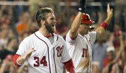 Washington Nationals Bryce Harper, left, and Ryan Zimmerman cheer on teammate Ian Desmond after scoring on his three-run double during the sixth inning of a baseball game against the Colorado Rockies at Nationals Park, on Monday, June 30, 2014, in Washington. (AP Photo/Evan Vucci)