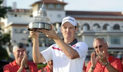Justin Rose, of England, poses with the trophy after he won the Quicken Loans National golf tournament, Sunday, June 29, 2014, in Bethesda, Md. Rose won in a one-hole playoff. (AP Photo/Nick Wass)