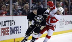 Detroit Red Wings' Tomas Tatar (21), of Slovakia, tries to get to the puck controlled by Pittsburgh Penguins' Matt Niskanen (2) during the second period of an NHL hockey game Thursday, March 20, 2014 in Detroit. The Red Wings defeated the Penguins 5-4 in overtime. (AP Photo/Duane Burleson)