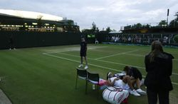 Madison Keys of U.S. receives treatment on court 12 as darkness falls during her match against Yaroslava Shvedova of Kazakhstan during their women's singles match at the All England Lawn Tennis Championships in Wimbledon, London, Saturday, June 28, 2014. (AP Photo/Ben Curtis)