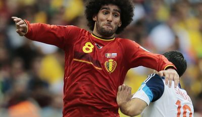 Belgium's Marouane Fellaini, left, challenges Russia's Alexander Samedov during the group H World Cup soccer match between Belgium and Russia at the Maracana stadium in Rio de Janeiro, Brazil, Sunday, June 22, 2014. (AP Photo/Ivan Sekretarev)