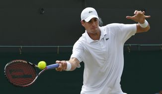 John Isner of U.S. plays a return to Feliciano Lopez of Spain during their men's singles match at the All England Lawn Tennis Championships in Wimbledon, London, Monday, June 30, 2014. (AP Photo/Pavel Golovkin)