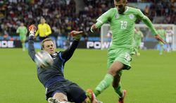 Germany's goalkeeper Manuel Neuer, left, slides in to make a save against Algeria's Islam Slimani during the World Cup round of 16 soccer match between Germany and Algeria at the Estadio Beira-Rio in Porto Alegre, Brazil, Monday, June 30, 2014. (AP Photo/Matthias Schrader)
