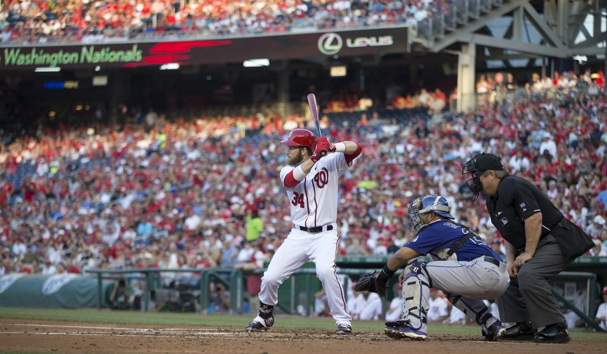 Washington Nationals left fielder Bryce Harper (34) waits for a pitch in his first at bat since returning from the disabled list during the second inning of a baseball game against the Colorado Rockies at Nationals Park, on Monday, June 30, 2014, in Washington. Harper is returning to the lineup after missing 59 games with a torn ulnar collateral ligament in his left thumb. At right is Colorado Rockies catcher Wilin Rosario. (AP Photo/ Evan Vucci)