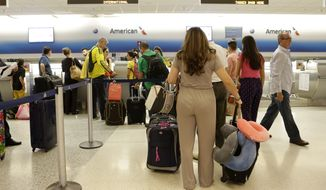 In this photo taken Wednesday, June 25, 2014, passengers wait in line at the American Airlines International counter at Miami International Airport in Miami. American Airlines announced that it will cut nearly 80 percent of its flights to Venezuela in a dispute over revenue being held by the South American country. American said that beginning July 2 it will operate 10 flights per week instead of the current 48. And it will only fly to Venezuela from Miami, scrapping flights from New York, Dallas and San Juan, Puerto Rico. (AP Photo/Alan Diaz)