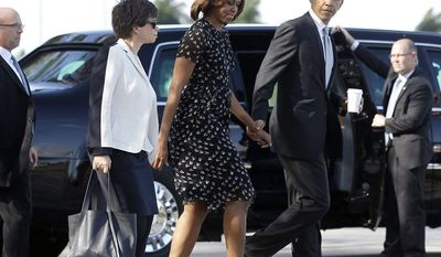 President Barack Obama walks with first lady Michelle Obama, center, and White House Senior Adviser Valerie Jarrett, left, to Marine One helicopter, after speaking at Coral Reef high school in Miami, Friday, March 7, 2014, and is heading onto Ocean Reef Club in Key Largo, Fla., to begin their weekend vacation. White House spokesman Josh Earnest defended Obama's trip to Key Largo, despite the ongoing crisis in Ukraine, arguing Obama would be able to monitor events from Florida.(AP Photo/Pablo Martinez Monsivais)