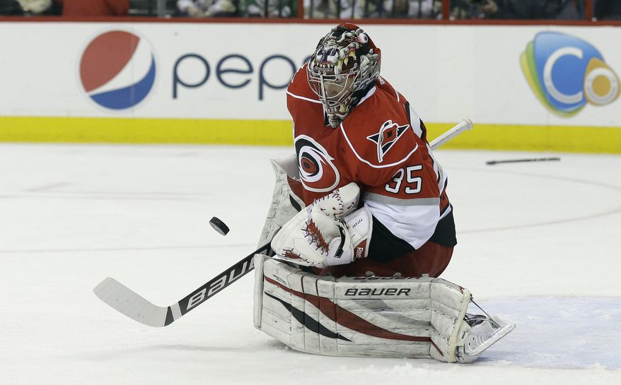 Carolina Hurricanes goalie Justin Peters (35) deflects a shot on goal during the first period of an NHL hockey game against the Pittsburgh Penguins in Raleigh, N.C., Tuesday, April 9, 2013. (AP Photo/Gerry Broome)