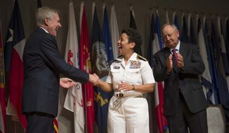 Secretary of the Navy Ray Mabus, left, congratulates Adm. Michelle Howard after putting on her fourth star during her promotion ceremony at the Women in Military Service for America Memorial. Howard is the first woman to be promoted to the rank of admiral in the history of the Navy and will assume the duties and responsibilities as the 38th Vice Chief of Naval Operations from Adm. Mark Ferguson. Howard's husband, Wayne Cowles, is at right.  (AP Photo/ Chief Mass Communication Specialist Peter D. Lawlor)