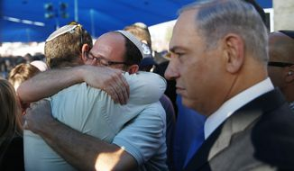 Israeli Prime Minister Benjamin Netanyahu, right, stands next to Avi Fraenkel, left, and Ori Yifrah, fathers of two of the three Israeli teens who were abducted and killed in the West Bank as they hug during their sons' joint funeral in the Israeli city of Modiin, Tuesday, July 1, 2014. Tens of thousands of mourners converged Tuesday in central Israel for the funeral service for three teenagers found dead in the West Bank after a two week search and crackdown on the Hamas militant group, which Israeli leaders have accused of abducting and killing the young men. The deaths of Eyal Yifrah, 19, Gilad Shaar, 16, and Naftali Fraenkel, a 16-year-old with dual Israeli-American citizenship, have prompted angry calls for revenge and Prime Minister Benjamin Netanyahu convened his security Cabinet for an emergency meeting to discuss a response to the killings, hours after airstrikes targeted dozens of suspected Hamas positions in the Gaza Strip.(AP Photo/Baz Ratner, Pool)