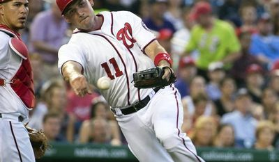 Washington Nationals catcher WIlson Ramos, left, looks on as third baseman Ryan Zimmerman fields a bunt for a base hit by Colorado Rockies Brandon Barnes during the fifth inning of a baseball game at Nationals Park, on Monday, June 30, 2014, in Washington. (AP Photo/Evan Vucci)