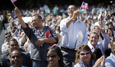 Hector Colon, left, and Victor Duran, right, both of the Dominican Republic, wave American flags after being sworn in during a naturalization ceremony for more than 1,000 citizenship candidates at Turner Field, home of the Atlanta Braves baseball team, Wednesday, July 2, 2014, in Atlanta. (AP Photo/David Goldman) ** FILE **