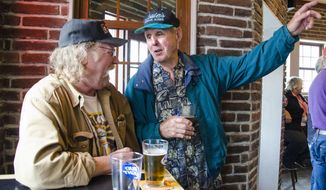 Louie Pusich, past owner of Louie's Douglas Inn from 1974 to 1996, enjoys a drink with John Shedd, foreman of the renovation of the bar, at its opening on Tuesday, July 1, 2014. The bar, seized by the federal government for failure to pay taxes, has a new owner and a new look.  (AP Photo/The Juneau Empire, Marlena Sloss)