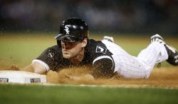 Chicago White Sox's Conor Gillaspie safely dives back to first after teammate Dayan Viciedo lined out against the Los Angeles Angels during the eighth inning of the second baseball game of a double header on Tuesday, July 1, 2014, in Chicago. (AP Photo/Andrew A. Nelles)