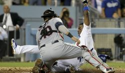 Los Angeles Dodgers' Dee Gordon, right, is tagged out at home by Cleveland Indians catcher Yan Gomes after Adrian Gonzalez lined into a triple play during the fourth inning of a baseball game in Los Angeles, Tuesday, July 1, 2014. (AP Photo/Chris Carlson)