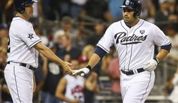 San Diego Padres' Carlos Quentin, right, is congratulated by Seth Smith after his two-run home run against the Cincinnati Reds in the seventh inning of a baseball game Tuesday, July 1, 2014, in San Diego. (AP Photo/Lenny Ignelzi)