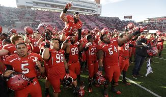** FILE ** In this Nov. 30, 2013, file photo, Utah players celebrate at the end of their NCAA college football game against Colorado, in Salt Lake City. The University of Utah has tweaked its official fight song, offering an alternate choice for its signature line while replacing others altogether amid concerns the former version was sexist. (AP Photo/Rick Bowmer, File)