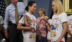 New York City Mayor Bill de Blasio watches hot dog eating contestants Miki Sudo, left, and Sonya Thomas, right, during a news conference to promote the upcoming Nathan's Famous Fourth of July Hot-Dog Eating Contest tomorrow Thursday, July 3, 2014, at City Hall in New York. (AP Photo/Frank Franklin II)