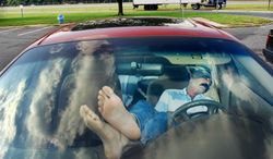 FILE - In this Sept. 25, 2003 file photo, an unidentified man rests his feet on the dashboard as he takes nap at a New Jersey Turnpike rest stop in Mount Laurel, N.J. The Centers for Disease Control and Prevention released its latest drowsy driving report on Thursday, July 3, 2014. According to a new survey, about 1 in 25 adults say they recently fell asleep while driving. (AP Photo/Daniel Hulshizer, File)