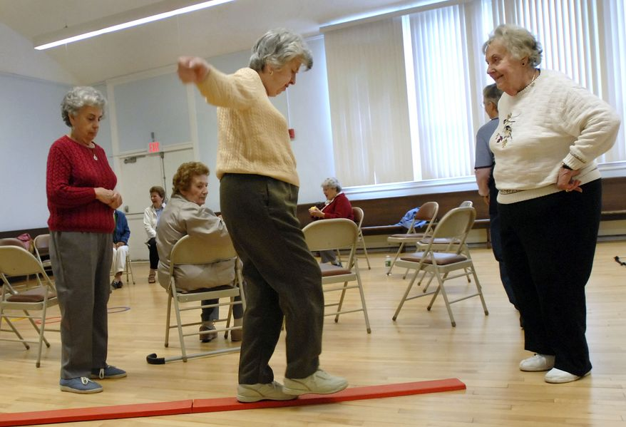 **FILE** Shirley Ristau (right) coaches Johanna O'Neill (center) through a balance obstacle course while O'Neill's sister, Mary O'Neill (left), looks on during a fall prevention demonstration class at the Manchester Senior Center in Manchester, Conn., on April 25, 2007. As deaths from fall-related injuries have skyrocketed nationwide, officials from several states, universities and hospitals are doing more help elderly people avoid falling. (Associated Press)