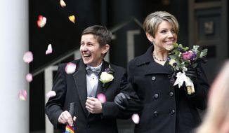 **FILE** Newlyweds Heather Laird (left) and Dawn Rains smile as flower petals are tossed their way as they depart Seattle City Hall on Dec. 9, 2012. Gov. Chris Gregoire signed a voter-approved law legalizing gay marriage on Dec. 5. (Associated Press)