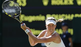 Eugenie Bouchard of Canada plays a return to Simona Halep of Romania during their women's singles semifinal match at the All England Lawn Tennis Championships in Wimbledon, London, Thursday, July 3, 2014. (AP Photo/Ben Curtis)