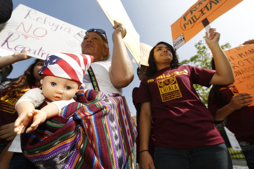Immigration activists Amarily Ortiz, left, and Mayra Sixtos, demand the Mexican government to take more measures to protect and respect the rights of unaccompanied minors and families crossing Mexico's territory during a protest outside the Mexican Consulate in Los Angeles Thursday, July 3, 2014. Activists demand support of migrant children and families Thursday, two days after U.S. Homeland Security buses carrying the migrants were routed away from American flag-waving protesters in Murrieta, Calif., and transported to a facility in San Diego. (AP Photo/Damian Dovarganes)
