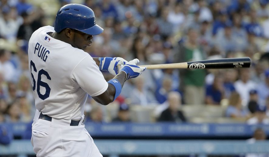 Los Angeles Dodgers right fielder Yasiel Puig hits a double against the Cleveland Indians during the first inning of a baseball game in Los Angeles, Tuesday, July 1, 2014. (AP Photo/Chris Carlson)
