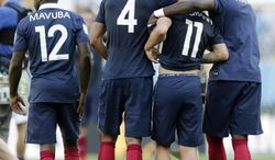 From left, France's Rio Mavuba, Raphael Varane, Antoine Griezmann and Eliaquim Mangala walk off the pitch after Germany defeated France 1-0 to advance to the semifinals during the World Cup quarterfinal soccer match at the Maracana Stadium in Rio de Janeiro, Brazil, Friday, July 4, 2014.  (AP Photo/Matthias Schrader)